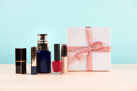Makeup cosmetics with gift box on wooden table.