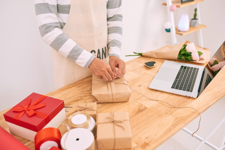 Asian man wrapping purchase while working in shop of gifts. Standard-Bild