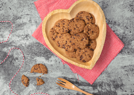 Traditional chocolate chip cookies on heart shape plate.