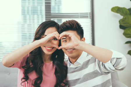 Asian couple sitting close to each other and looking through a heart shape made with their fingers