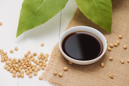 Soy sauce and soy bean on wooden table