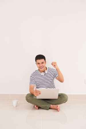 Casual asian man sitting on floor using laptop at home in the living room