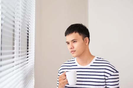 young man having a cup of coffee while looking out of the window at home. Stock Photo - 93884974