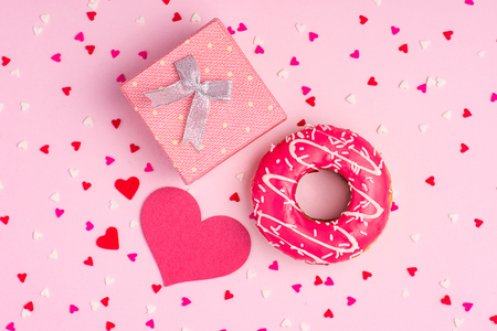 Delicate pink party background with streamers for celebrating with scattered confetti and donut. Stock Photo
