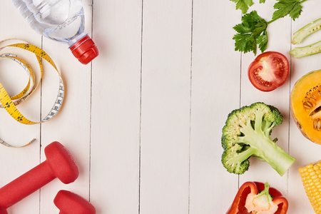 Bell pepper with measuring tape, dumbbells and bottle of water, isolated on white Stock Photo - 93680705