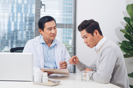 Doctor explaining prescription to male patient, healthcare concept Stock Photo