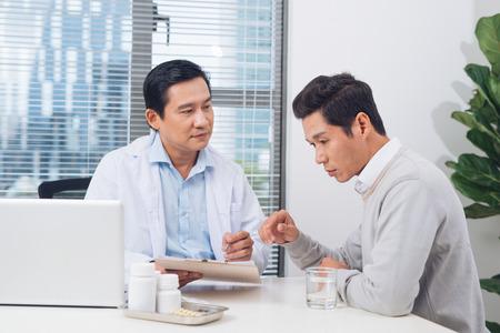 Doctor explaining prescription to male patient, healthcare concept Foto de archivo