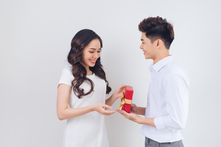 Love. Handsome young Vietnamese man giving present to beautiful woman at home Foto de archivo