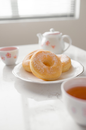 Classic donut. Morning breakfast with tea on table in living room at home.