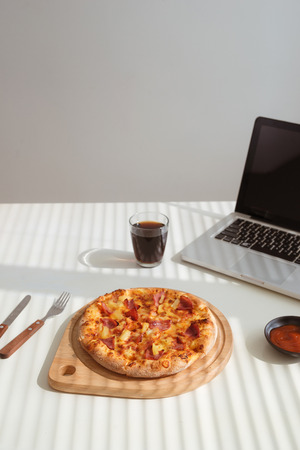 Tasty pizza on office desk with coke and laptop, fast food