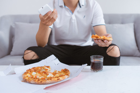 Asian man enjoying his pizza while sitting on couch watching tv at home. Banque d'images
