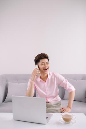 Junger hübscher asiatischer Mann mit Laptop am Telefon