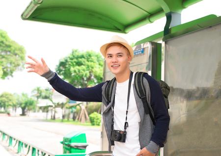 ハンサムな若いアジアの男は、彼のバスを待って、笑顔
