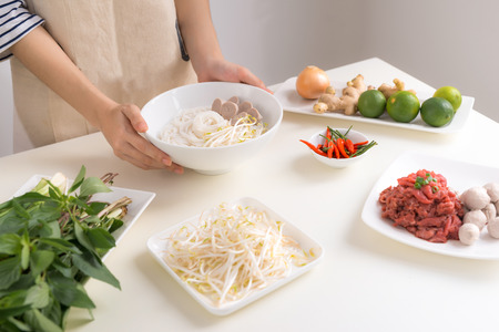 Female chef prepare traditional Vietnamese soup Pho bo with herbs, meat, rice noodles