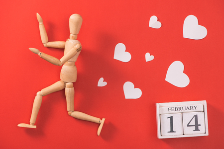 Wooden man figure running to escape from love.