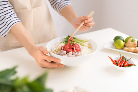 Female chef prepare traditional Vietnamese soup Pho bo with herbs, meat, rice noodles Stok Fotoğraf - 93858733