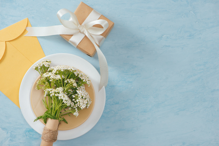 Tet Holiday Concept. Gold Envelope (Lucky money) on table with Table setting with Plate and Flowers.