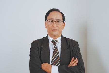 Zekere hogere Aziatische bedrijfsleider die zich in het bureau bevindt Stockfoto