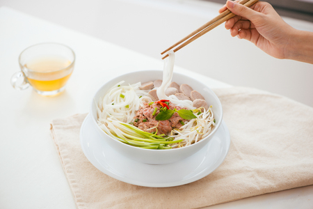Woman eating traditional Vietnamese Pho noodle using chopsticks. Banque d'images