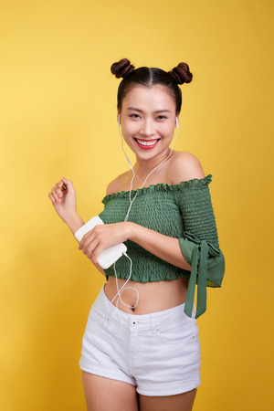 Beautiful young asian woman in headphones listening to music and singing on yellow background