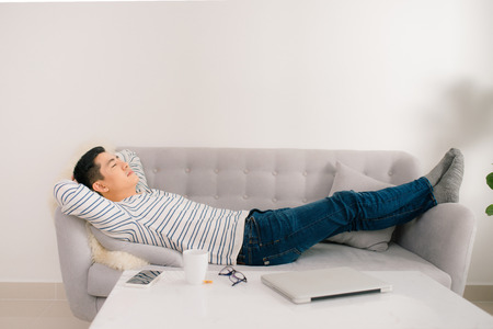 Young handsome asian man sleeping on sofa.