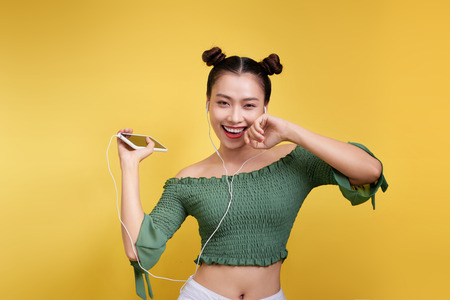 Colorful studio portrait of happy young asian woman with earphones is dancing and singing. Stock Photo