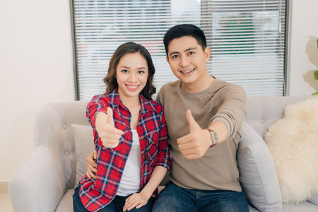 Young asian couple with thumbs up in new home 版權商用圖片
