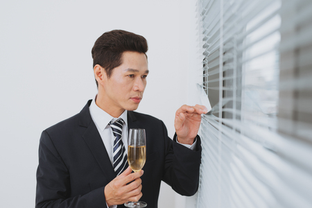 Smiling young businesman with glass of champagne standing by the window. Stock Photo