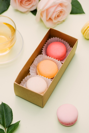 Colorful macaroons and rose flowers with tea on light green. Sweet macarons in gift box. Top view