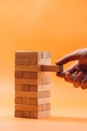 Businessman gambling placing wooden block on a tower Stock Photo