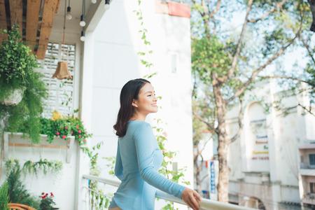 Beautiful asian girl enjoying the freshness on balcony Stockfoto