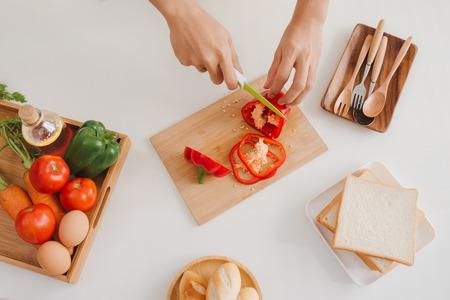 新鮮な赤ピーマンをスライスする男性の手