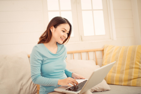 Happy casual beautiful asian young woman working on a laptop at home.