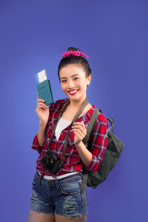 Woman travel. Young beautiful asian woman traveler with passport on blue background