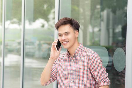 Confident asian man talking on smart phone standing outside the office Zdjęcie Seryjne - 94797127