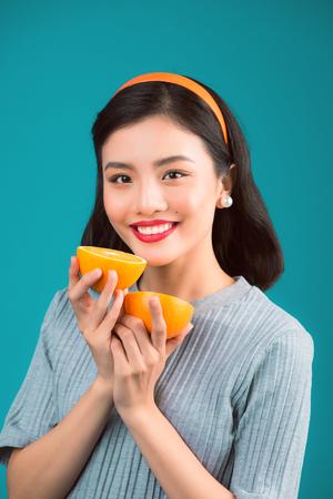 健康的な食べ物。青い背景の上にオレンジを保持して素敵なピンナップアジアの女の子を笑顔。 写真素材