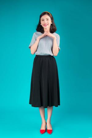 Tout le corps d'une femme asiatique souriante vêtue d'une robe de style pin-up sur bleu. Banque d'images - 94688121
