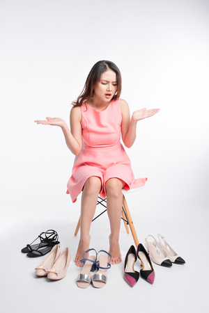 Pretty young asian woman trying on a few pairs of high heels 版權商用圖片