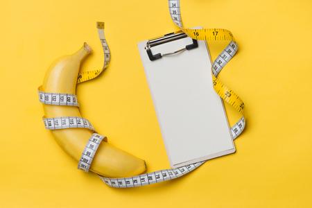 黄色の背景に白紙でバナナの周りに巻かれた測定テープ,ダイエットの概念. 写真素材