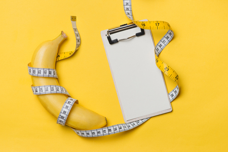 Measuring tape wrapped around a banana with blank paper on a yellow background, Concept of diet. Stock fotó