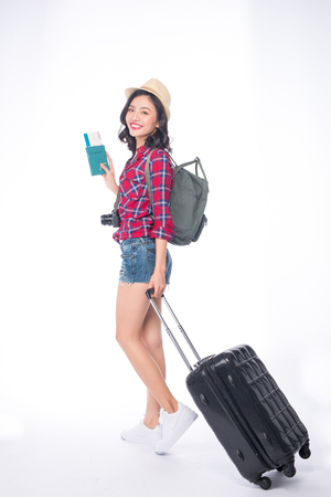 Woman travel. Young beautiful asian woman traveler with suitcase and camera on white background Archivio Fotografico