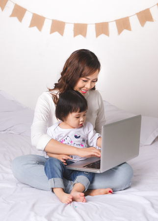 Asian lady in classic suit working on laptop at home with her baby girl.