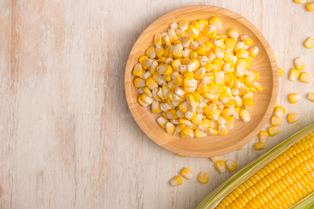 Sweet corn seeds on a wooden plate  Stock fotó