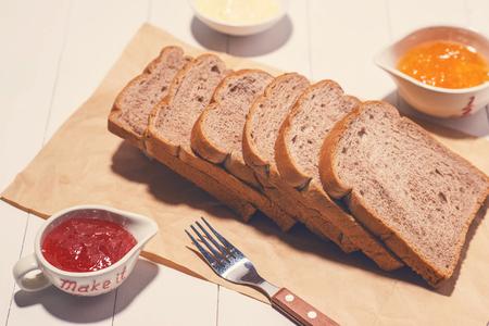 나무 테이블에 잼과 버터 토스트 빵 조각의 근접