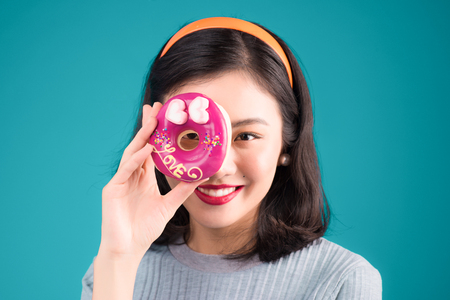 Asiatisches Schönheitsmädchen, das rosa Donut gegen ihr Auge hält. Retro frohe Frau mit Bonbons, Nachtisch, der über blauem Hintergrund steht.