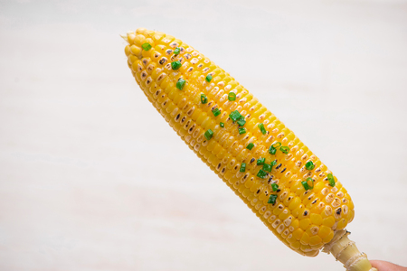 Delicious tasty grilled corn on wooden table