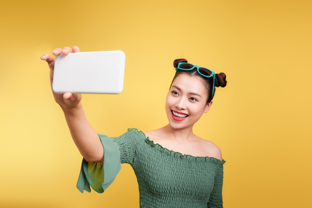 Young cheerful attractive asian woman taking selfies with smile. Stock Photo