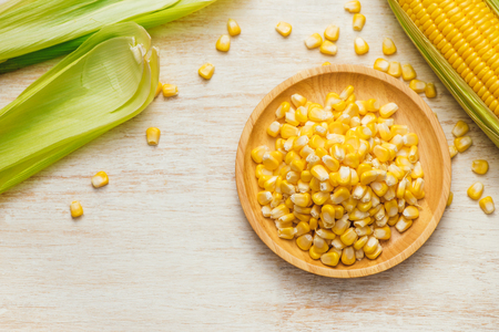 Sweet corn seeds on a wooden plate Stock Photo - 94522144