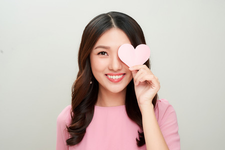 Beautiful asian woman smiling and showing pink heart shape. Loving concept.