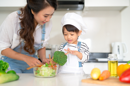 Happy family in the kitchen. Mother and child daughter are preparing the vegetables and fruit. Stock Photo